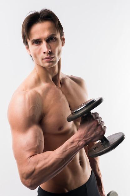 Uomo atletico con corpo muscoloso che tiene pesi Foto Gratuite