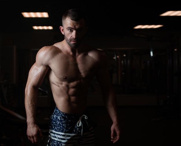 Uomo atletico con un corpo muscoloso pone in palestra, mostrando i suoi muscoli. Foto Premium