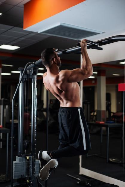 Uomo atletico facendo esercizi di pull-up su una traversa in palestra Foto Premium
