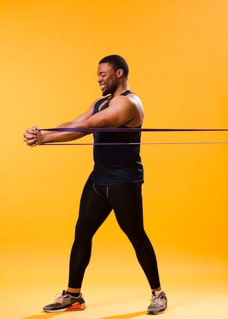 Uomo atletico in attrezzatura della palestra che si esercita con la banda di resistenza Foto Gratuite