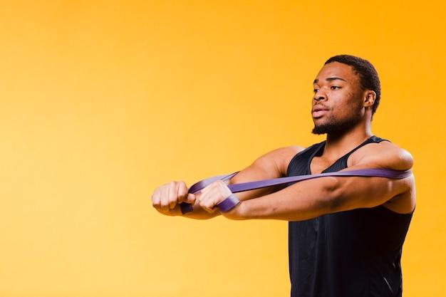Uomo atletico in attrezzatura della palestra con lo spazio della banda e della copia di resistenza Foto Gratuite