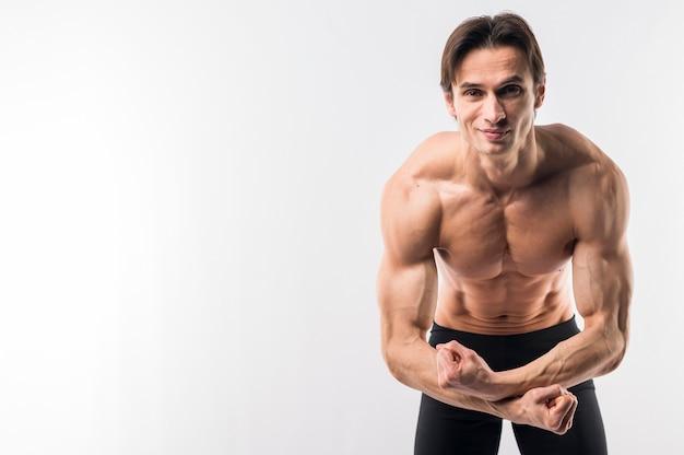 Uomo atletico senza camicia che ostenta armi muscolose con lo spazio della copia Foto Gratuite