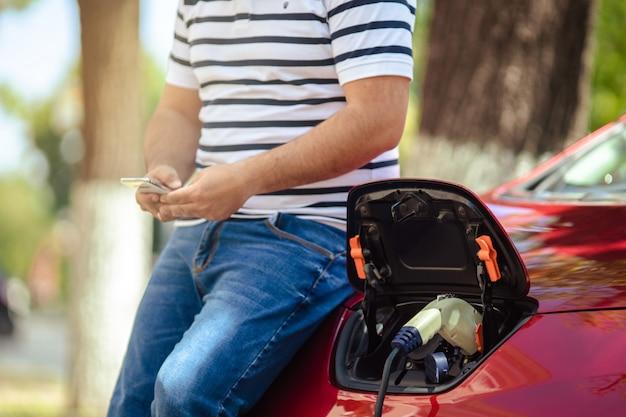 Uomo attento all'ambiente che carica il suo veicolo elettrico. Foto Premium