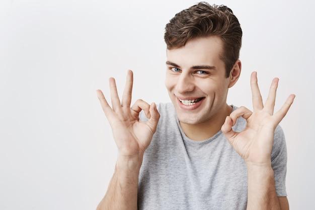 Uomo attraente con gli occhi azzurri, sorridendo con gioia che mostra segno giusto con entrambe le mani, felice dopo l'incontro con la sua ragazza isolata. espressioni ed emozioni facciali umane Foto Gratuite