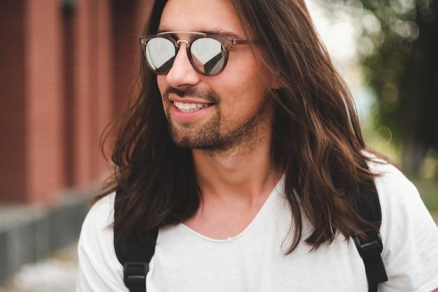 Uomo attraente del ritratto con gli occhiali da sole sul sorridere urbano di scena Foto Gratuite
