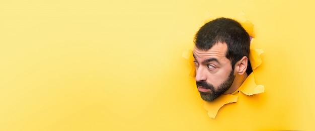 Uomo attraverso una carta bucata Foto Premium