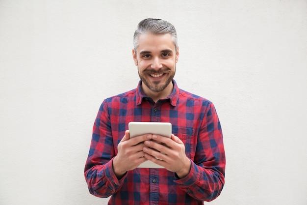 Uomo barbuto allegro con tablet pc Foto Gratuite