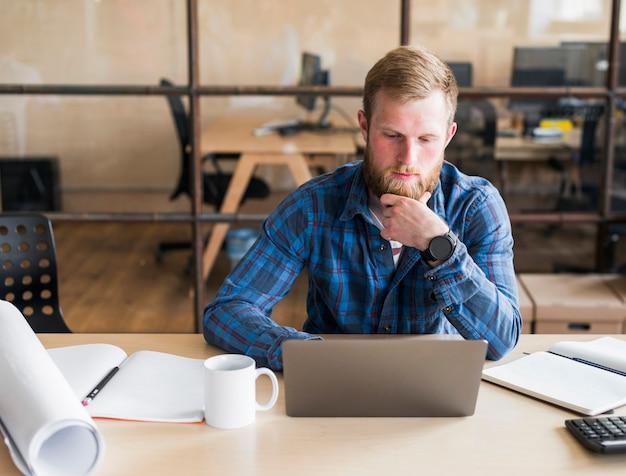 Uomo barbuto che lavora al computer portatile sul posto di lavoro Foto Gratuite