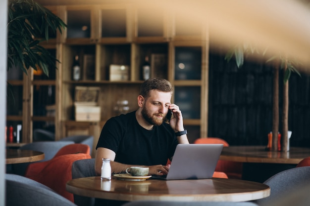 Uomo barbuto che si siede in un caffè bevendo caffè e lavorando su un computer Foto Gratuite