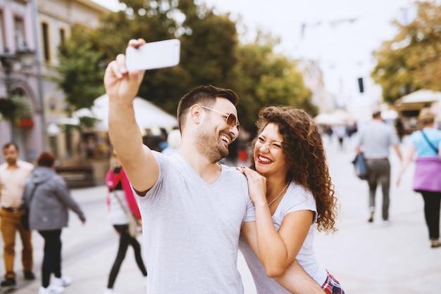 Uomo barbuto con occhiali da sole prendendo un selfie con una splendida ragazza con i capelli ricci. Foto Premium
