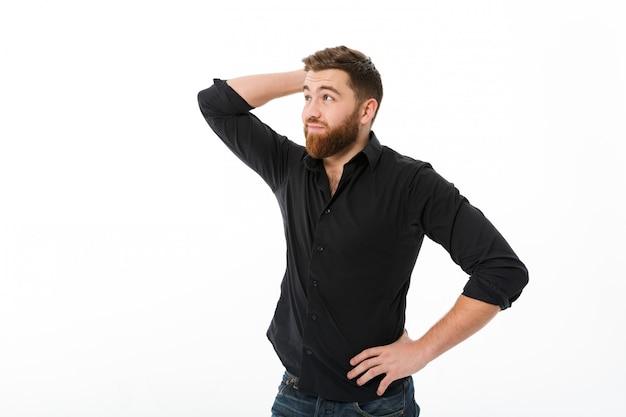 Uomo barbuto confuso in camicia che tiene la testa e guardando lontano Foto Gratuite