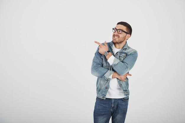 Uomo barbuto emozionante felice in occhiali che esaminano macchina fotografica con il sorriso e che indicano via Foto Gratuite
