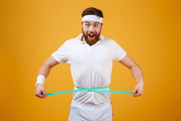 Uomo barbuto felice di forma fisica che misura la sua vita con nastro adesivo Foto Gratuite