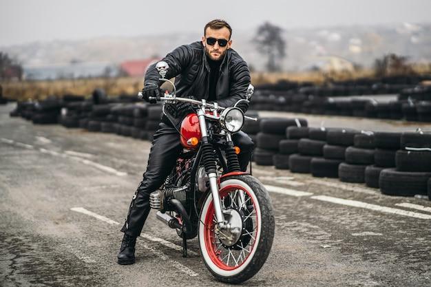 Uomo barbuto in occhiali da sole e giacca di pelle che esamina la macchina fotografica mentre era seduto su una moto sulla strada. dietro di lui c'è una fila di pneumatici Foto Premium