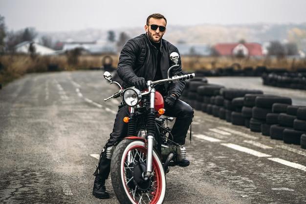 Uomo barbuto in occhiali da sole e giacca di pelle seduto su una moto sulla strada. Foto Premium