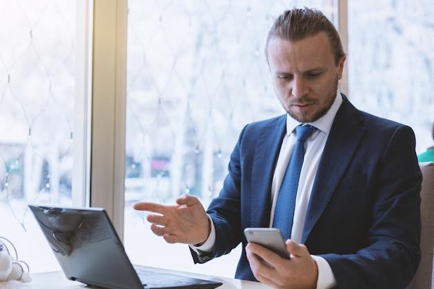 Uomo barbuto nel vestito guardando un telefono cellulare con uno sguardo sorpreso al coperto Foto Premium