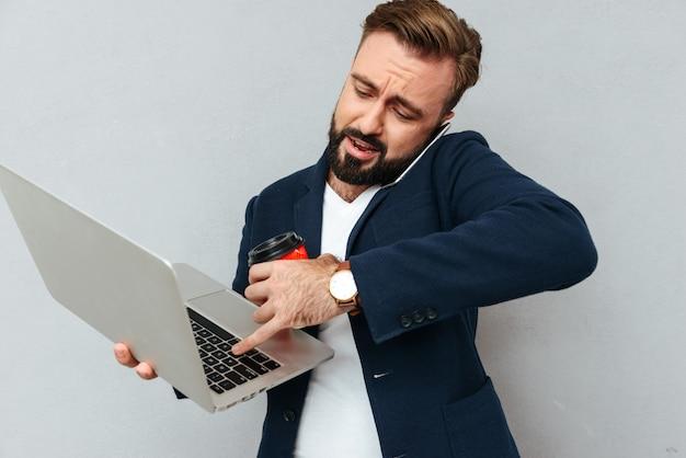 Uomo barbuto occupato in vestiti di affari che parla dallo smartphone Foto Gratuite