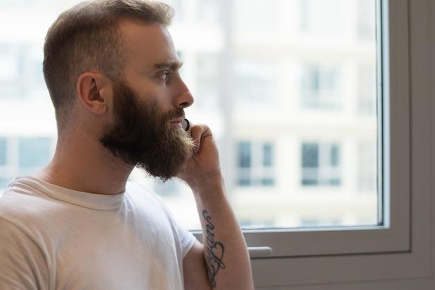 Uomo barbuto pensoso che comunica sul telefono e che osserva fuori finestra Foto Gratuite