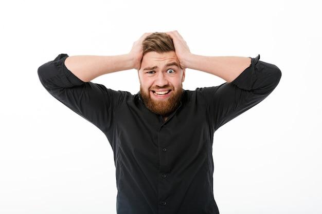 Uomo barbuto preoccupato in camicia che tiene la sua testa Foto Gratuite