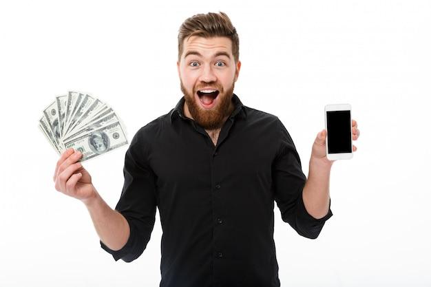 Uomo barbuto sorpreso felice di affari in soldi della tenuta della camicia Foto Gratuite