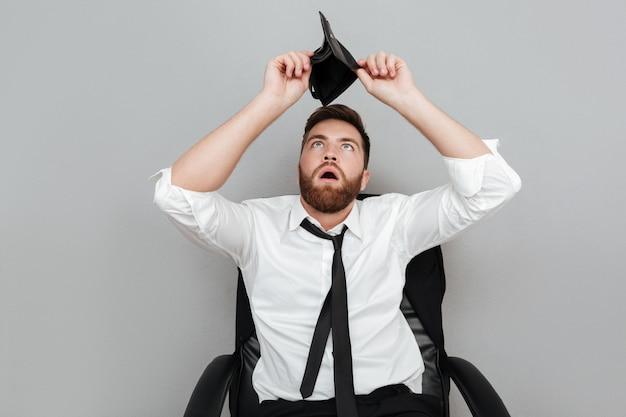 Uomo barbuto sorpreso frustrato in camicia bianca che mostra portafoglio vuoto Foto Gratuite