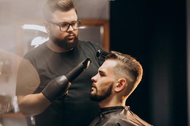 Uomo bello ad un negozio di barbiere che disegna capelli Foto Gratuite