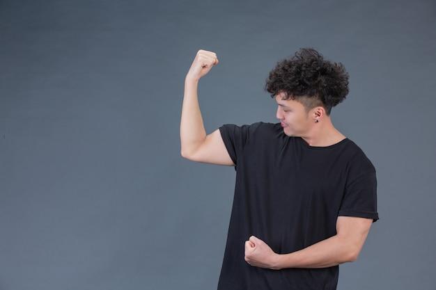 Uomo bello allo studio che mostra i muscoli delle braccia Foto Gratuite