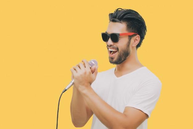 Uomo bello asiatico con i baffi, sorridente e cantando al microfono isolato su sfondo giallo Foto Premium