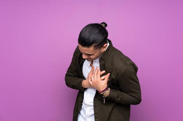 Uomo bello asiatico sulla parete blu che ha un dolore nel cuore Foto Premium