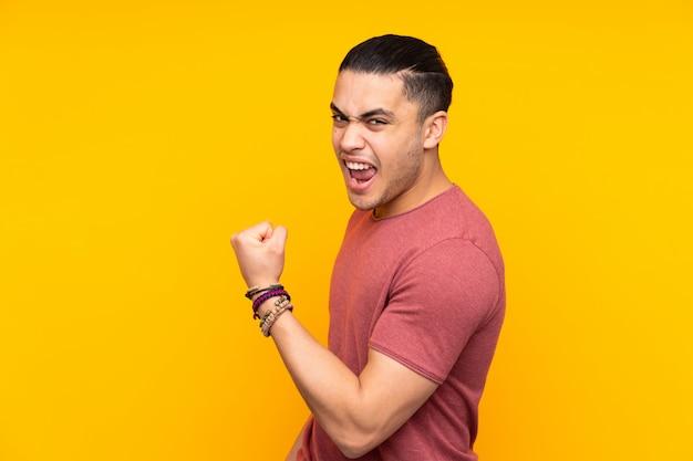 Uomo bello asiatico sulla parete gialla con l'espressione di sorpresa mentre indicando lato Foto Premium