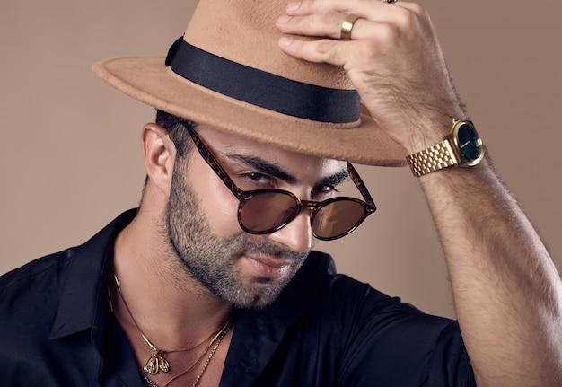 Uomo bello brutale abbronzato hipster in camicia nera, cappello e occhiali Foto Premium