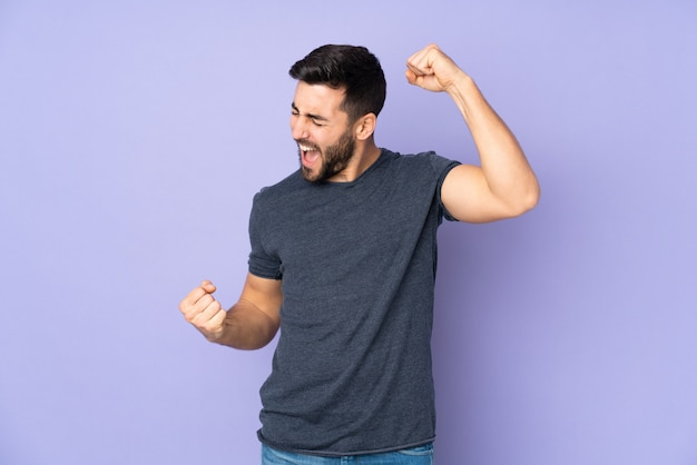 Uomo bello caucasico che celebra una vittoria sopra la parete viola isolata Foto Premium
