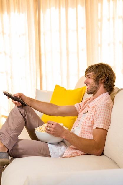 Uomo bello che guarda la tv e mangia pop corn seduto sul divano Foto Premium