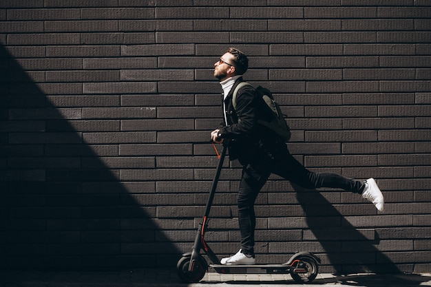 Uomo bello che guida in città su scooter Foto Gratuite