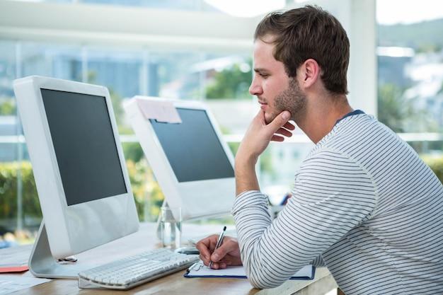Uomo bello che lavora al computer e che prende le note in un ufficio luminoso Foto Premium