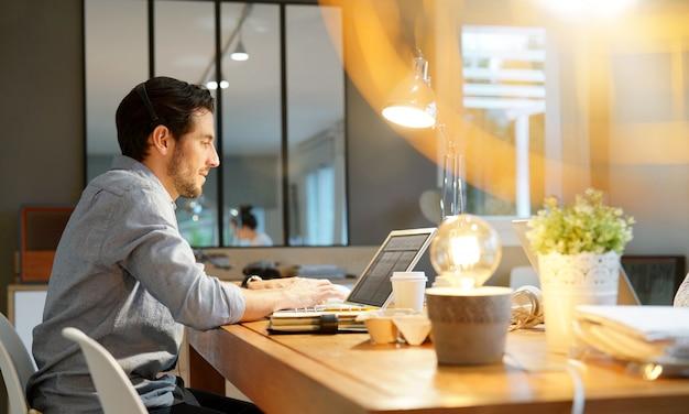 Uomo bello che lavora al computer portatile in co spazio di lavoro Foto Premium