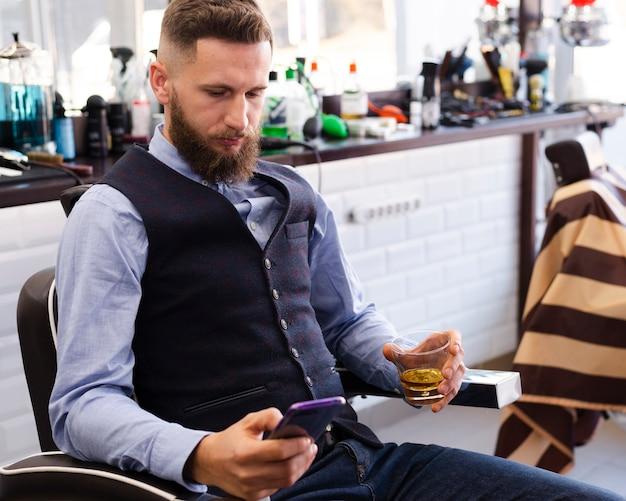 Uomo bello che osserva sul suo telefono il negozio di barbiere Foto Gratuite