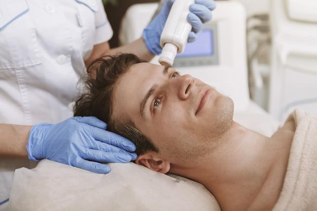 Uomo bello che ottiene trattamento facciale di cura della pelle Foto Premium