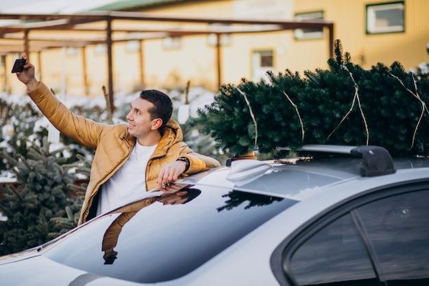 Uomo bello che parla sul telefono in macchina con l'albero di natale in cima Foto Gratuite
