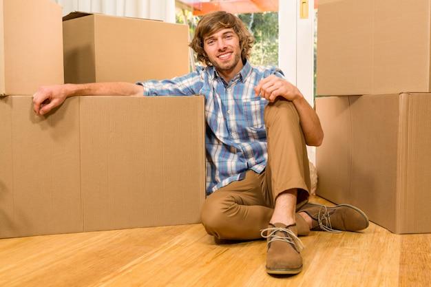 Uomo bello che posa con le scatole commoventi nella sua nuova casa Foto Premium