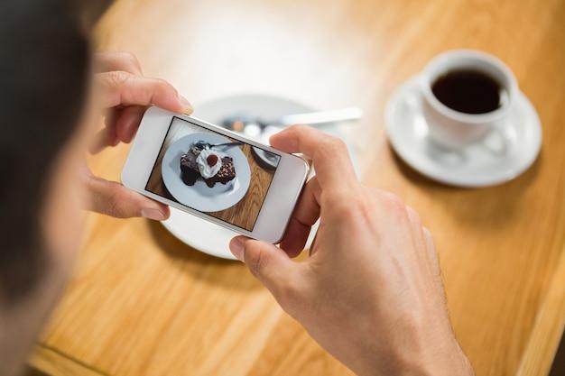 Uomo bello che prende un'immagine del suo alimento Foto Premium