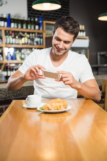 Uomo bello che prende un'immagine del suo panino Foto Premium