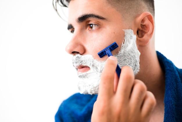 Uomo bello che rade il suo primo piano della barba Foto Gratuite