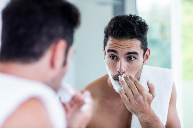 Uomo bello che rade la sua barba in bagno Foto Premium