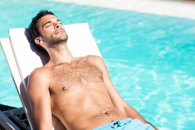 Uomo bello che riposa sulla sedia a sdraio a bordo piscina Foto Premium