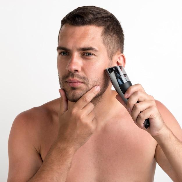 Uomo bello che si rade con il regolatore elettrico isolato su fondo bianco Foto Gratuite