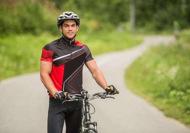 Uomo bello che sta con la sua bicicletta sul sentiero forestale. Foto Premium