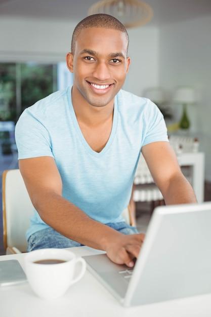 Uomo bello che utilizza computer portatile nella cucina Foto Premium