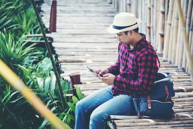 Uomo bello che utilizza computer portatile nella natura di viaggio Foto Gratuite