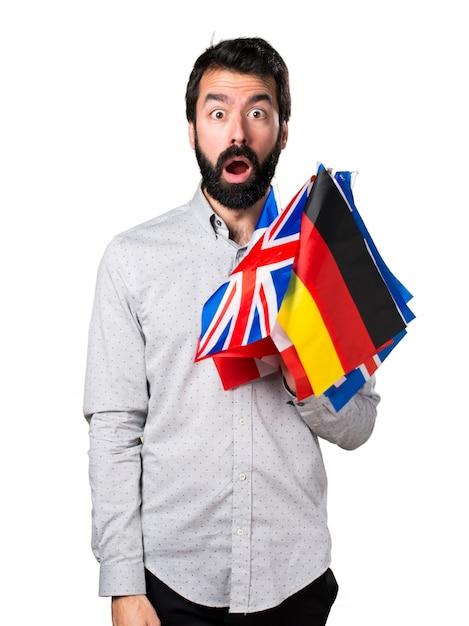 Uomo bello con la barba che detiene molte bandiere e facendo gesto di sorpresa Foto Gratuite